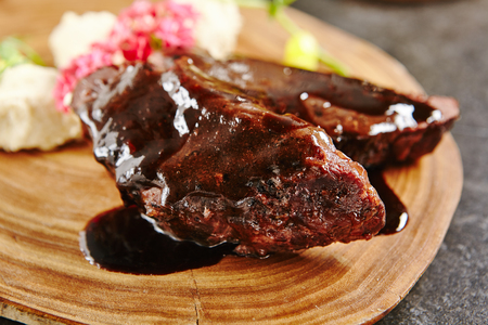 Meat Main Course with Grilled Lamb Cheeks Poured with Demi Glace Sauce, Cheese and Vegetables. Roasted Mutton on Rustic Wooden Background Closeup Stock Photo