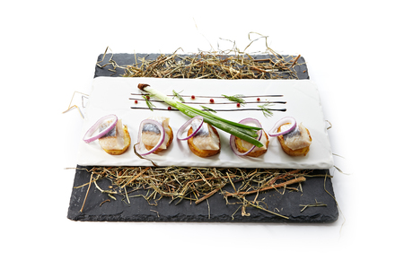 Herring Canape with Potato and Onion on Natural Rustic Background. Beautiful Creative Sea Food Design of Fish Fillet with Scallions on Dry Hay and Black Slate Stock Photo