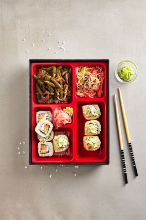 Fresh Food Portion in Japanese Bento Box with Sushi Rolls, Salad and Main Course Top View. Asian Style Lunch Box with Nori Maki Set, Meat, Cooked Vegetables, Rice Noodles, Pickled Ginger and Wasabi Stock fotó