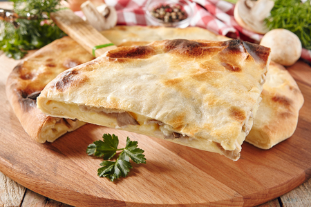 Fresh Baked Piece of Pie Stuffed with Mushrooms and Potatoes Close Up with Selective Focus. Slice of Delicious Vegetarian Champignon Cake Serving with Green Parsley on Old Wooden Vintage Background Stock Photo
