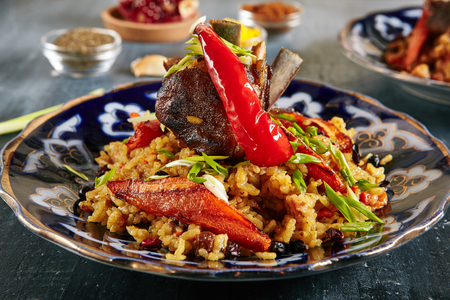 Pilau or Pilaf with Lamb Meat Close Up Selective Focus. Traditional Asian Dish Plov also known as Polow, Pilav, Pallao, Pulao, Palaw with Rice, Spices, Vegetables and Fried Veal