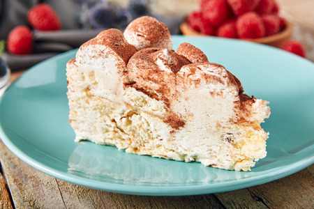 Triangular Slice of Tiramisu with Coffee, Mascarpone Cheese and Cocoa on Vintage Background with Berries. Coffee Flavoured Italian Cream Dessert of Ladyfingers Layered with a Whipped Eggs and Sugar Stockfoto