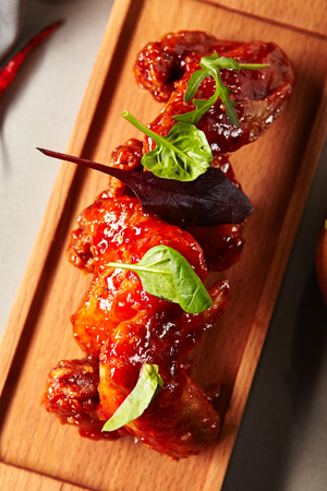 Close-up portrait of baked chicken wings with sweet and sour sauce. Delicious bits with golden crust. Selective focus and healthy concept. Served on wooden board