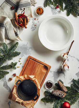 Vintage New Year Background with Empty Plate, Traditional Winter Spices, Herbs and Natural Cotton Branch on Gray Plaster Texture Top View. Retro Christmas Table with Place for Text or Copyspace 写真素材
