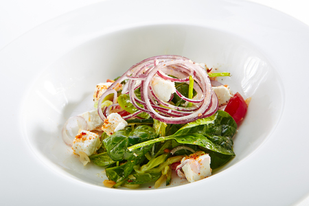 Green Salad with Goat Cheese, Spinach, Tomato and Red Onion Rings Isolated on White Background. Restaurant Starter Menu with fresh Spinacia and Chard Leaves, Tomatoes, Greens, Spices Close Up