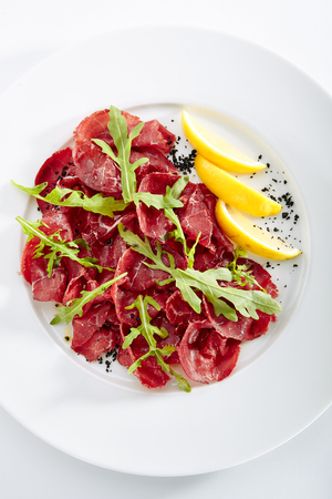Dried Italian Beef Bresaola, Lemon, Fresh Basil, Arugula and Balsamic Cream Top View. Air-dried and Salted Veal, Horse, Venison or Pork with Greens on Flat Restaurant Plate Standard-Bild - 115864702