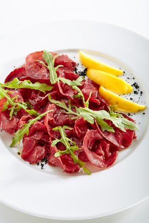 Dried Italian Beef Bresaola, Lemon, Fresh Basil, Arugula and Balsamic Cream Isolated on White Background. Air-dried and Salted Veal, Horse, Venison or Pork with Greens on Flat Restaurant Plate Standard-Bild - 115864703