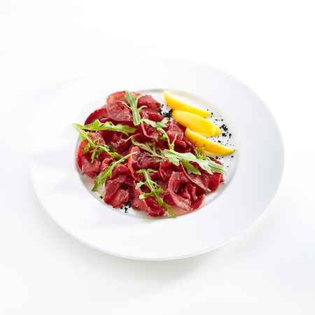 Dried Italian Beef Bresaola, Lemon, Fresh Basil, Arugula and Balsamic Cream Isolated on White Background. Air-dried and Salted Veal, Horse, Venison or Pork with Greens on Flat Restaurant Plate Standard-Bild - 115864707