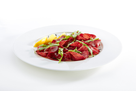 Dried Italian Beef Bresaola, Lemon, Fresh Basil, Arugula and Balsamic Cream Isolated on White Background. Air-dried and Salted Veal, Horse, Venison or Pork with Greens on Flat Restaurant Plate Standard-Bild - 115864710