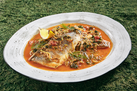 Beautiful Serving Vintage Ceramic Bowl of Azeri Syrdak with Sea Bass, Vegetables and Leek on Natural Moss and Wood Background. Homemade Asian Seafood Dish with Whole Fish in Red Spicy Sauce Close Up Standard-Bild - 115864743