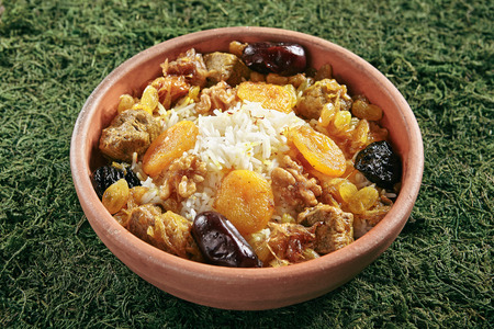 Beautiful Serving Vintage Ceramic Bowl of Turshu with Rice, Lamb Meat, Walnuts, Dried Fruits and Fragrant Saffron on Natural Moss and Wood. Homemade Mutton Fillet with Sweet Dates and Prunes Standard-Bild - 115864782