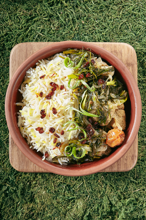 Beautiful Serving Vintage Ceramic Bowl of Roast Meat with Rice and Herbs Top View. Homemade Grilled Beef, Lamb Fillet with Onions, Raisins, Dried Fruits and Greens on Natural Moss and Wood Standard-Bild - 115864783