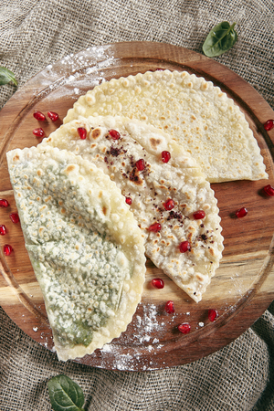 Set of Kutabs on Rustic Tablecloth Burlap Background. Qutab, Kutab or Gozleme is Thinly Rolled Dough with Cheese and Greens that is Cooked Briefly on a Convex Griddle Top View Standard-Bild - 115864801
