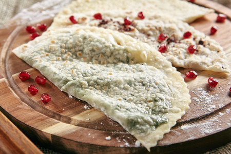 Set of Kutabs on Rustic Tablecloth Burlap Background. Qutab, Kutab or Gozleme is Thinly Rolled Dough with Cheese and Greens that is Cooked Briefly on a Convex Griddle Standard-Bild - 115864807