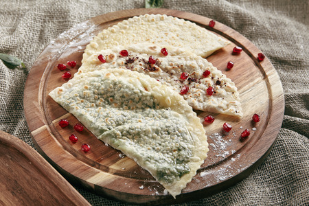 Set of Kutabs on Rustic Tablecloth Burlap Background. Qutab, Kutab or Gozleme is Thinly Rolled Dough with Cheese and Greens that is Cooked Briefly on a Convex Griddle Standard-Bild - 115864820