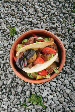 Beautiful Serving Vintage Ceramic Bowl of Lamb with Oriental Spices in Wine Sauce and Cake Top View. Original Restaurant Homemade Mutton Meat with Tomatoes, Zucchini, Basil and Flatbread on Rustic Background Standard-Bild - 115864830