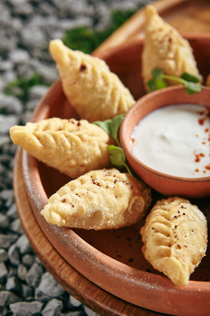 Azerbaijani Fried Dumplings Giurza with Minced lamb Meat also known as Gyoza, Dim Sum, Jiaozi, Momo, Mandu or Ravioli Close Up. Hot Crunchy Beef and Mutton Pelmeni on Natural Rustic Bakground