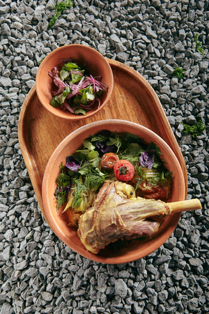 Beautiful Serving Homemade Buglama or Shin of Lamb with Vegetables and Fragrant Herbs in Vintage Ceramic Bowl Top View. Traditional Hot Ragout with Mutton Meat with Greens and Spices on Rustic Background