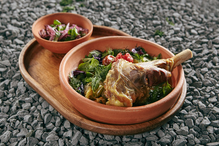 Beautiful Serving Homemade Buglama or Shin of Lamb with Vegetables and Fragrant Herbs in Vintage Ceramic Bowl. Traditional Hot Ragout with Mutton Meat with Greens and Spices on Rustic Background Standard-Bild - 115864839