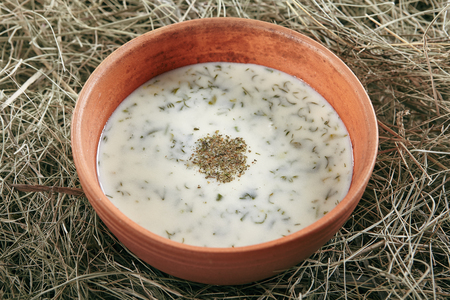 Beautiful Serving Vintage Ceramic Bowl of Homemade Kefir Soup Dovga or Tarator. National Sour-Milk Meal of Azerbaijani Cuisine with Yogurt, Herbs and Greens on Rustic Background Close Up Standard-Bild - 115864844