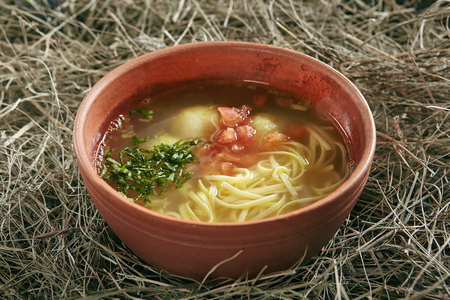 Beautiful Serving Vintage Ceramic Bowl of Homemade Noodle Soup Arishta with Chicken Meatballs. Clear Sturdy Seasoned Broth with Turkey Meat Balls, Egg Spaghetti and Greens on Rustic Background Standard-Bild - 115864846