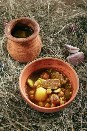 Homemade Lamb Soup Piti or Putuk with Cherry Plums in Vintage Ceramic Bowl on Rustic Background. Azerbaijani Bozbash with Mutton, Vegetables and Spices or Clear Sturdy Seasoned Broth Close Up Standard-Bild - 115864847