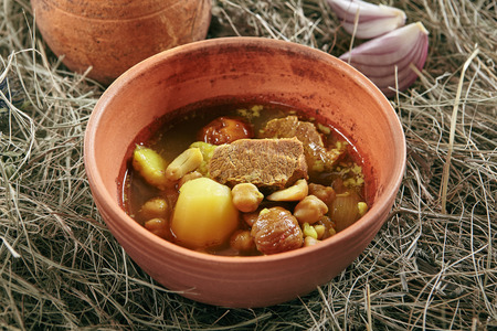 Homemade Lamb Soup Piti or Putuk with Cherry Plums in Vintage Ceramic Bowl on Rustic Background. Azerbaijani Bozbash with Mutton, Vegetables and Spices or Clear Sturdy Seasoned Broth Close Up Standard-Bild - 115864848