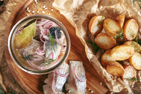 Marinated Herring in Vinegar with Potatoes, Oil, Dill, Onion and Spices on Rustic Background Top View. Beautiful Creative Sea Food Vintage Design of Pickled Fish Fillet with Baked Potato on a Wooden Tray Standard-Bild - 115864869