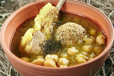 Homemade Kufta Bozbash Mutton Soup with Vegetables, Meat Balls and Spices in Vintage Ceramic Bowl. Azerbaijani Clear Sturdy Seasoned Broth with Fat Lamb, Peas and Meatballs on Rustic Background Standard-Bild - 115864885
