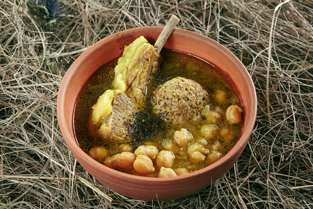 Homemade Kufta Bozbash Mutton Soup with Vegetables, Meat Balls and Spices in Vintage Ceramic Bowl. Azerbaijani Clear Sturdy Seasoned Broth with Fat Lamb, Peas and Meatballs on Rustic Background Standard-Bild - 115864888