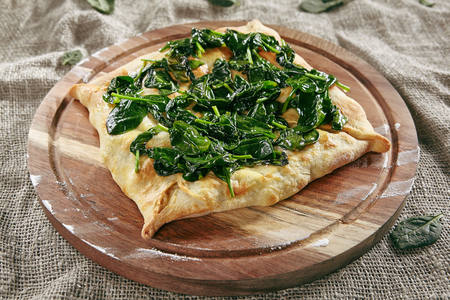 Homemade Square Khachapuri Made From a Delicious Tender Dough with Spinach, Melted Cheese and Butter Close Up. Traditional Hachapuri Topped with Spinacia Leaves on Wooden Rustic Background Standard-Bild - 115864889