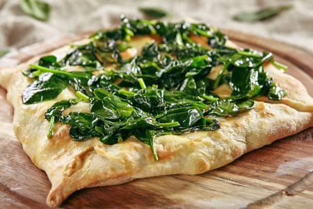Homemade Square Khachapuri Made From a Delicious Tender Dough with Spinach, Melted Cheese and Butter Close Up. Traditional Hachapuri Topped with Spinacia Leaves on Wooden Rustic Background Standard-Bild - 115864890