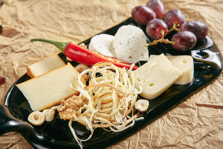 Wine Plate with Cheese Mix, Nuts and Grapes on White Rectangular Flat Plate. Cheeseboard with Pieces of Various Cheese such as Cheddar, Manchego, Gauda and Smoked Cheese Standard-Bild - 115864894
