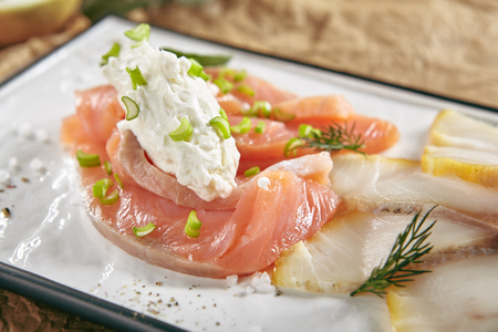 Exquisite Serving Restaurant Plate of Smoked Salted Raw White Fish Fillet with Red Fish Sashimi. Delicacy Fresh Seafood Dish with Toothfish, Salmon and Tuna Meat on Rustic Background Close Up Standard-Bild - 115864895