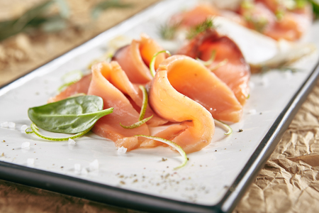 Exquisite Serving Restaurant Plate of Smoked Salted Raw White Fish Fillet with Red Fish Sashimi. Delicacy Fresh Seafood Dish with Toothfish, Salmon and Tuna Meat on Rustic Background Close Up Standard-Bild - 115864897