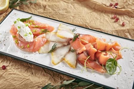 Exquisite Serving Restaurant Plate of Smoked Salted Raw White Fish Fillet with Red Fish Sashimi. Delicacy Fresh Seafood Dish with Toothfish, Salmon and Tuna Meat on Rustic Background Close Up Standard-Bild - 115864898