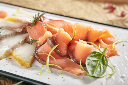 Exquisite Serving Restaurant Plate of Smoked Salted Raw White Fish Fillet with Red Fish Sashimi. Delicacy Fresh Seafood Dish with Toothfish, Salmon and Tuna Meat on Rustic Background Close Up Standard-Bild - 115864899