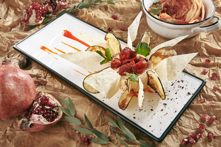 Exquisite Serving White Restaurant Plate of Eggplant Paste decorated With Eggplant Chips and Thin Slices of Pita Bread. Baba Ghanoush, Caponata, or Aubergine Caviar with Mashed Grilled Aubergines Standard-Bild - 115864901