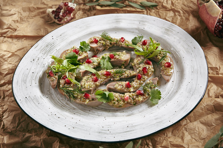 Delicatessen Dish of Lamb Tongues with Green Eastern Dressing on a Restaurant Plate Decorated with Greens, Sauce and Pomegranate Grain Standard-Bild - 115864904