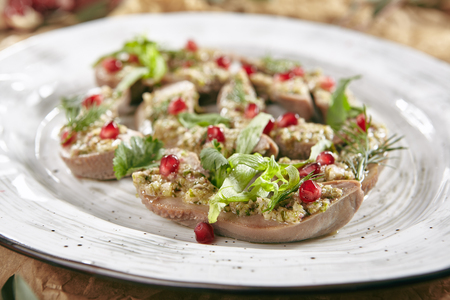 Delicatessen Dish of Lamb Tongues with Green Eastern Dressing on a Restaurant Plate Decorated with Greens, Sauce and Pomegranate Grain Standard-Bild - 115864934