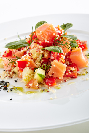 Restaurant Starter Menu with Raw Salted Salmon Slices, Tomato and Cucumber Isolated on White Background. Diced Red Fish or Trout with Vegetables, Herbs and Spices on Elegant Flat Plate Close Up Standard-Bild - 115864970