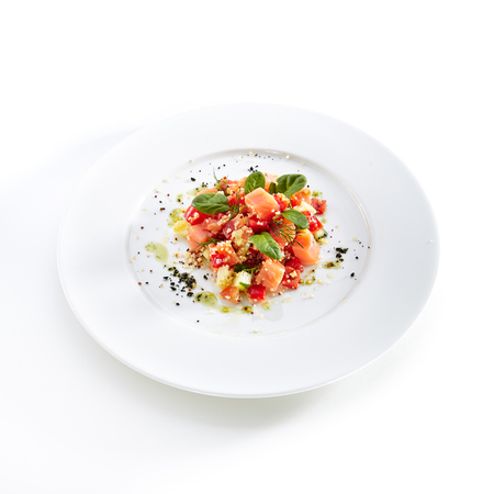 Restaurant Starter Menu with Raw Salted Salmon Slices, Tomato and Cucumber Isolated on White Background. Diced Red Fish or Trout with Vegetables, Herbs and Spices on Elegant Flat Plate Close Up Standard-Bild - 115864971