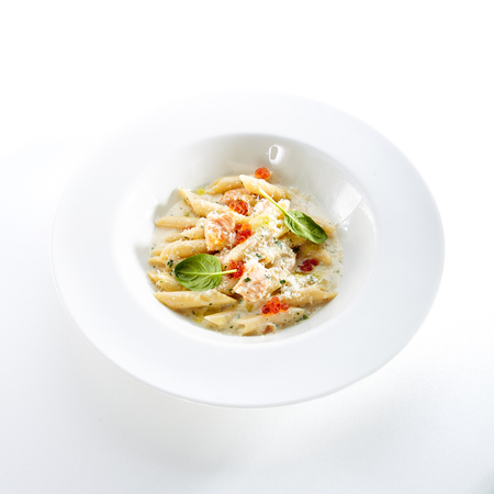 Fish Penne Pasta Al Dente with Salmon, Red Caviar, Parmigiano Reggiano Cheese, Spices and Basil in Restaurant Plate Isolated on White Background Close Up. Traditional Italian Macaroni Standard-Bild - 115864972