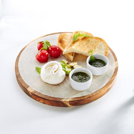 Burrata, Burata or Fresh Mozzarella Cheese with Cherry Tomatoes, Olive Oil, Balsamic Cream, Sea Salt, Pesto Sauce, Lime Peel, Basil and Ciabatta Isolated on White Background Close Up Standard-Bild - 115864977