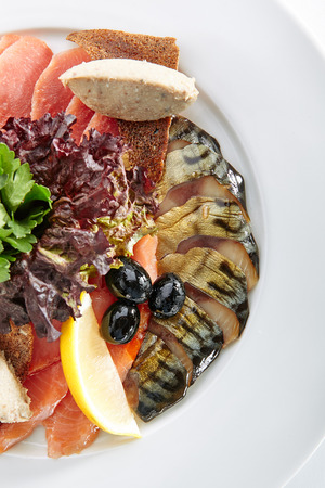Elegant Restaurant Plate with Fish Delicacies Top View. Smoked Butter Fish, Salmon, Perch, Marinated Dorado, Forshmak with Lemon, Olives, Quail Egg, Greens and Bread Crisps Standard-Bild - 115864979