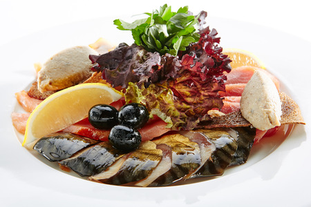 Elegant Restaurant Plate with Fish Delicacies. Smoked Butter Fish, Salmon, Perch, Marinated Dorado, Forshmak with Lemon, Olives, Quail Egg, Greens and Bread Crisps