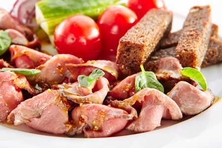 Thin Slices of Spicy Roast Beef with Fresh Vegetables. Restaurant Plate with Veal, Cucumbers, Cherry Tomatoes, Borodino Bread Toasts, Onion, Dijon Mustard Sauce, Greens Standard-Bild - 115864984