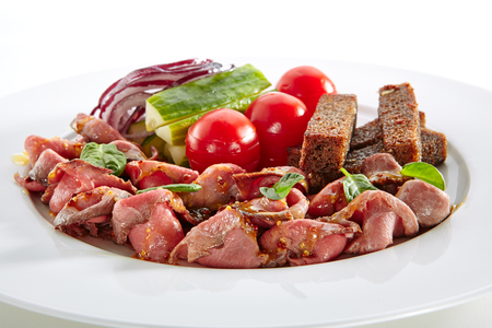 Thin Slices of Spicy Roast Beef with Fresh Vegetables Isolated on White Background. Restaurant Plate with Veal, Cucumbers, Cherry Tomatoes, Borodino Bread Toasts, Onion, Dijon Mustard Sauce, Greens Standard-Bild - 115864988