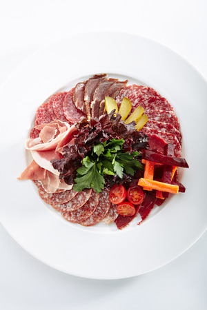 Antipasto with Sliced Ham, Salami Cured Meats, Pickled Meat, Greens, Tomatoes and Vegetables in Oil or Vinegar Isolated on White Background. Elegant Restaurant Plate with Italian Antipasti Top View Standard-Bild - 115864995