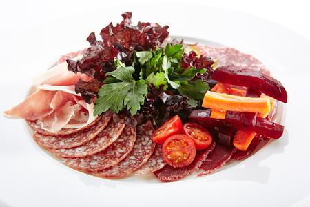 Antipasto con lonchas de jamón, salami, carnes en escabeche, verdes, tomates y verduras en aceite o vinagre aislado sobre fondo blanco. Placa de restaurante elegante con antipasti italiano de cerca